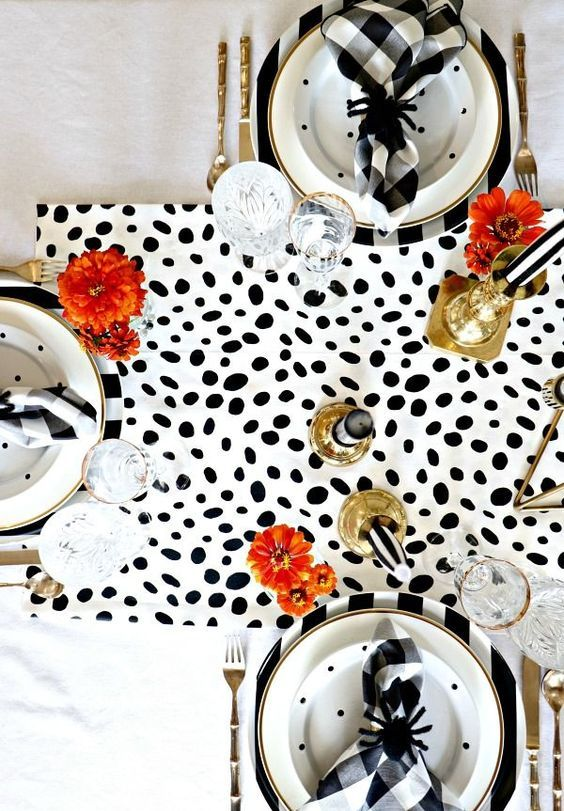 a modern glam Halloween tablescape with a Dolmatin runner, printed plates, brigth blooms, gold candleholders and black spiders