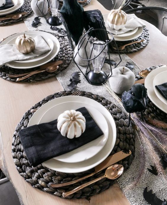 a modern rustic Halloween tablescape with woven placemats, painted apples and pears, candles and bulb lamps