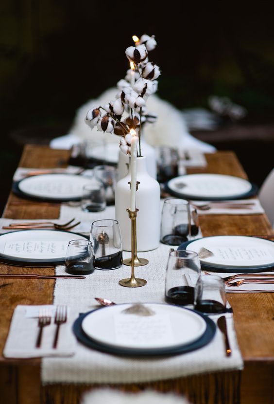 a monochromatic winter tablescape with a white runner and placemats, white vases with cotton, black chargers and black bottom glasses plus copper cutlery