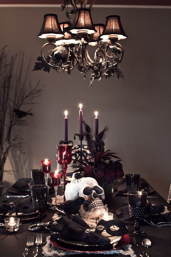 a moody and chic Halloween tablescape with black linens, purple candles and deep red blooms, skulls, crows, spiders and black goblets