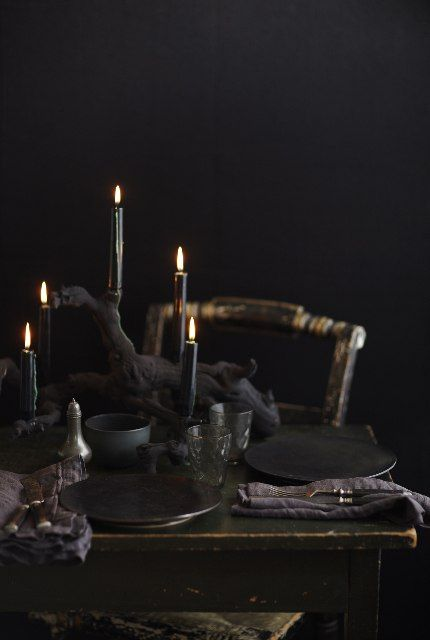 a moody black Halloween tablescape with black candles, plates, napkins, glasses and bowls is very chic