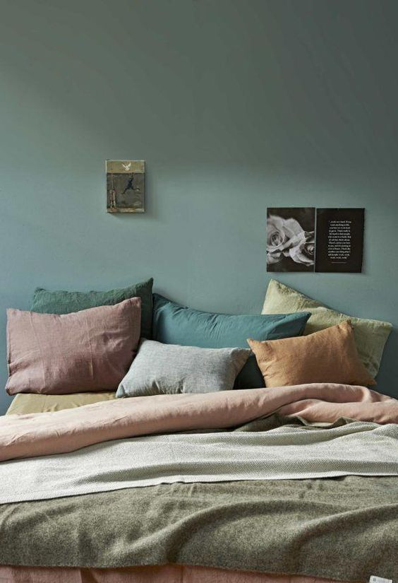 a muted-colored bedroom with a dark green wall, pillows of muted shades like rust, greens and mauve