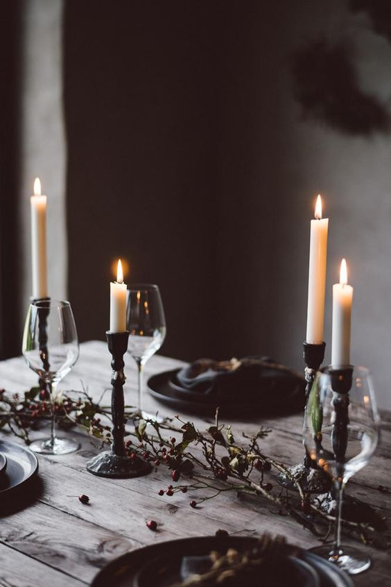 a natural Halloween table setting with candles, dried branches with berries, greenery and black plates
