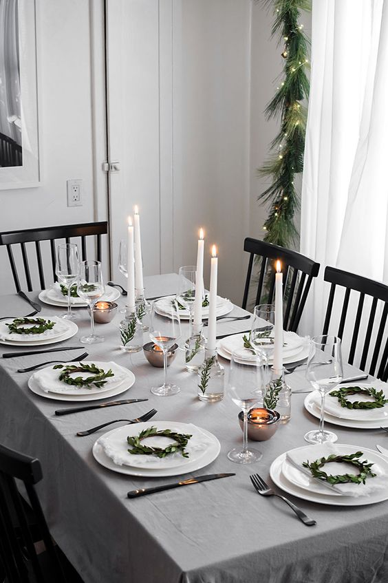 a neutral and simple winter tablescape with mini greenery wreaths for decor, candles in vases with greenery and mini tealights