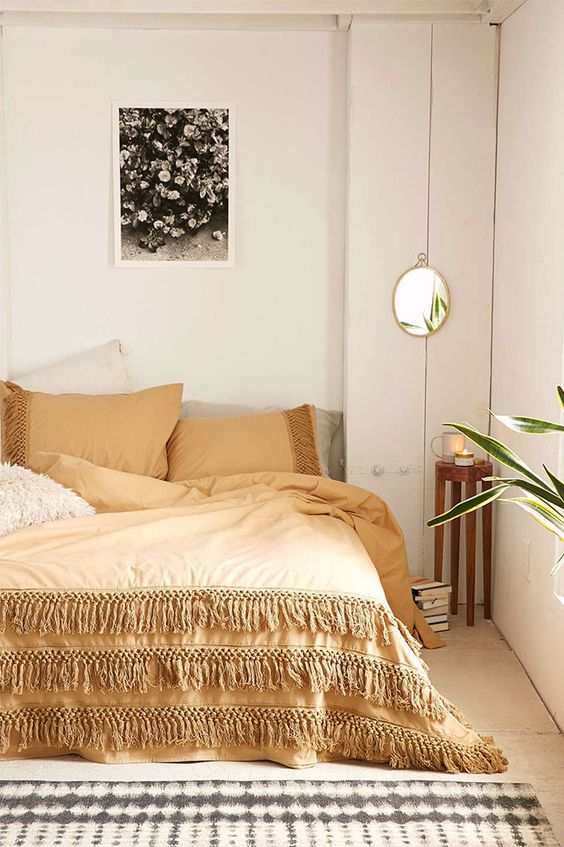 a neutral fall bedroom done in creamy, greys and touches of beige plus boho details