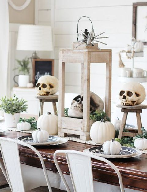 a neutral rustic Halloween tablescape with a woven runner, white pumpkins and skulls, greenery and succulents