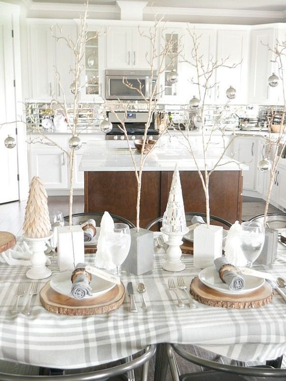 a neutral winter table with a plaid tablecloth, faux trees, mini trees with silver ornaments, wood slice placematts