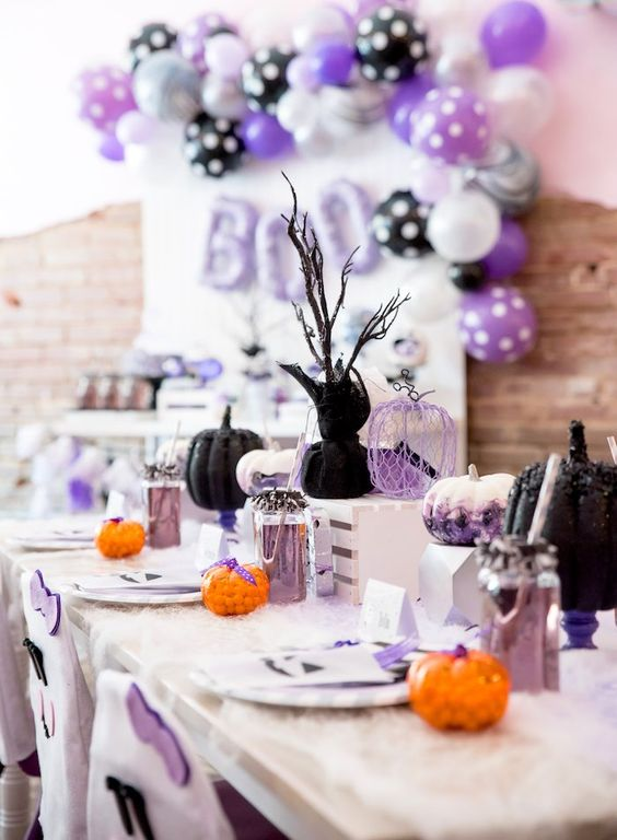 a pastel modern Halloween tablescape with black, watercolor and wire pumpkins, lavender lemonade and cutlery, candies and branches