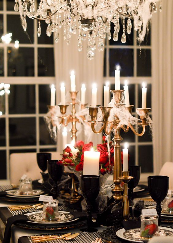 a refined Gothic tablescape with candles covered with spiderwebs, red roses, black goblets and plates, gold cutlery and candleholders