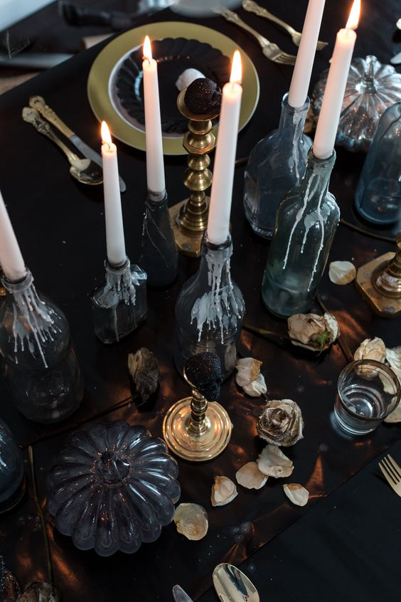 a refined Halloween tablescape with candles, dried petals, black pumpkins and touches of gold here and there