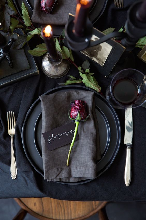 a refined black Halloween table setting with black linens, plates, candles, vintage books and photos, greenery and simple cutlery