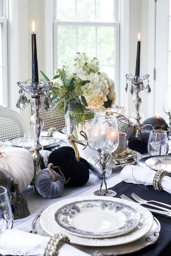 a refined black and white Halloween tablescape with velvet pumpkins, black candles, white blooms, printed plates