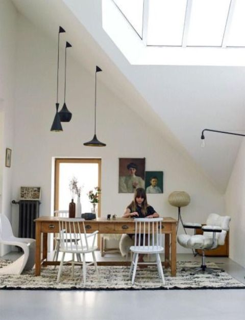 a refined eclectic attic home office with a skylight, a wooden desk, some mismatching chairs, blakc pendant lamps, refined artworks