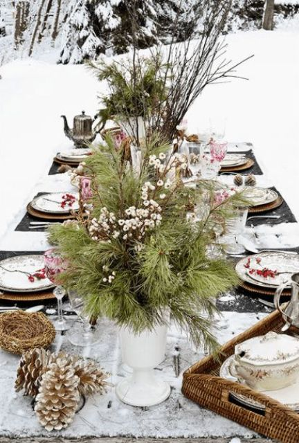 a rustic outdoor winter table with a white runner, an evergreen and berry centerpiece, snowy pinecones, berries for each palce setting