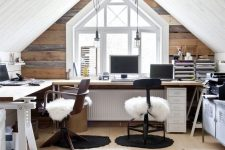 a shared rustic attic home office with a reclaimed wood accent wall, a corner desk, stained chairs, faux fur and pendant lamps