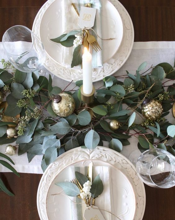 a simple and cute winter table with a greenery and gold ornament runner, white patterned porcelain and greenery and white berries on plates
