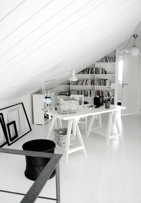 a small Scandinavian home office with a trestle desk, a bookshelf on the wall, some empty frames and a lamp