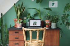 a small and chic attic home office with a green accent wall, a retro desk and a rattan chair, lots of plants and natural light coming through a skylight