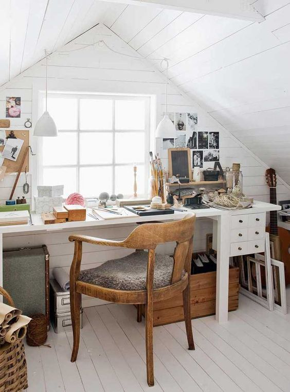 a small and cozy attic home office with white planked walls and a ceiling, a white desk with some drawers, a stained chair and some gallery walls