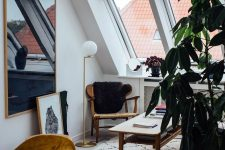 a small and elegant attic home office with a reading nook by the window, a wooden chair and a low coffee table, a desk and a mustard chair plus lots of skylights