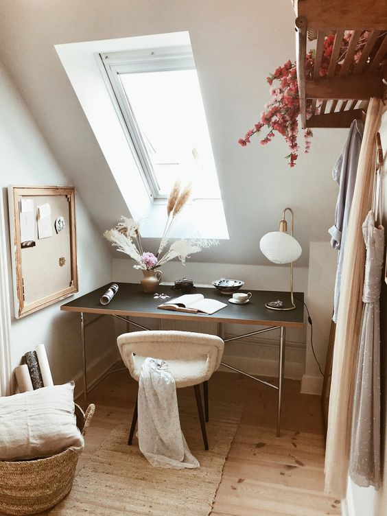 a small and lovely attic home office with a black desk by the skylight, a soft chair, a memo board, a basket with a pillow is cozy