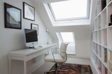 a small and sleek white attic home office with a narrow white desk and leather chair, a large storage unit, two skylights and a gallery wall