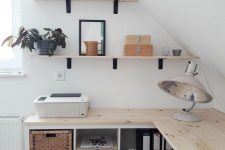 a small attic Nordic home office with floating desk with storage, wall-mounted shelves, cool lamps and a comfy chair