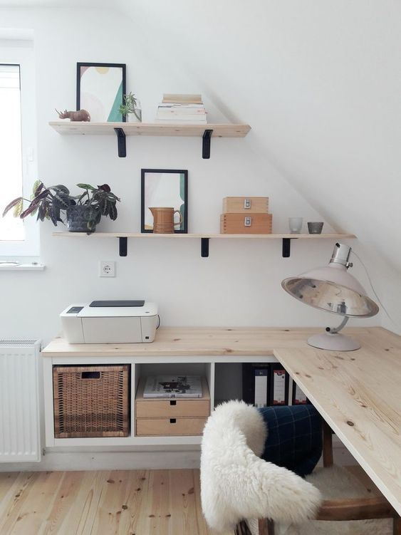 a small attic Nordic home office with floating desk with storage, wall mounted shelves, cool lamps and a comfy chair
