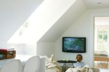 a small attic home office with a TV nook, a white shared desk and white chairs, a TV and beanbag chairs plus a large skylight