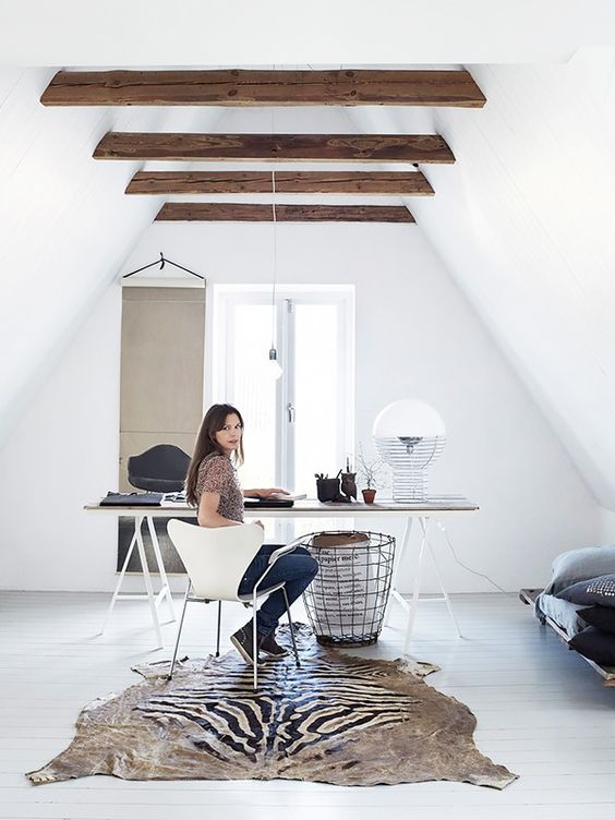 a small attic home office with wooden beams on the ceiling, an airy trestle desk, a white chair, a creative rug, a metal basket and a sofa in the corner