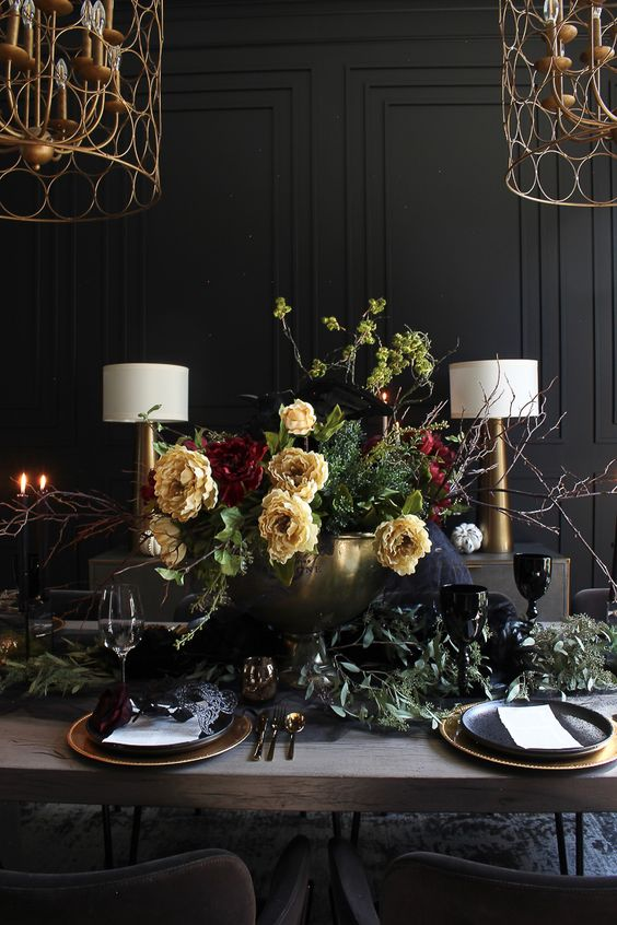 a sophisticated Halloween tablescape with yellow and burgundy blooms, eucalyptus, gold chargers and cutlery, candles