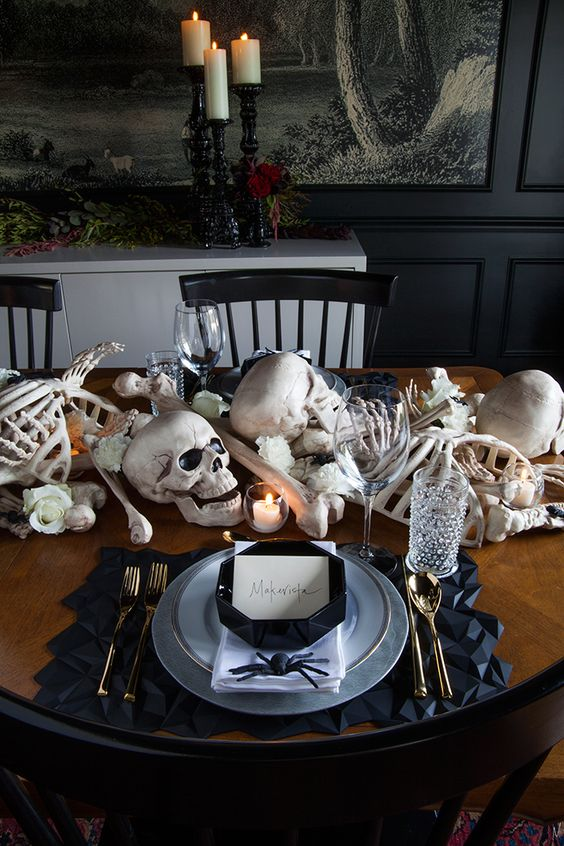 a stylish Halloween tablescape with bones, skulls, candles, white blooms, black geometric placemats and plates, gold cutlery