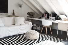 a stylish Nordic attic home office with a planked ceiling and floor, layered rugs, a couple of white sofas and a long shared desk plus a couple of chairs