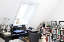 a stylish Scandinavian home office with wooden beams, a vintage black desk, a black leather chair, a large bookshelf, some rugs and pillows