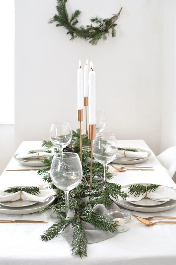 a stylish and fresh winter table with a snowy evergreen and pinecone runner, evergreens, gold cutlery and a matching wreath on the wall