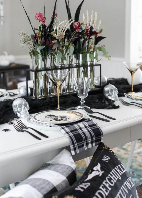 a stylish blackm white and silver Halloween tablescape with a black runner, plaid napkins, silver skulls, spiders and bold blooms