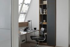 a stylish contemporary attic home office with a sleek desk, a black leather chair, some built-in storage units and a cool table lamp