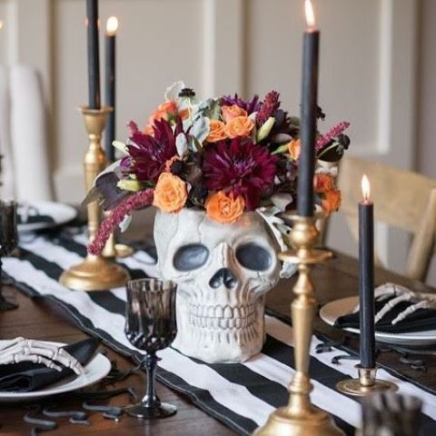 a stylish modern Halloween table setting with bold blooms in a skull, deep toned candles, black and white linens and skeleton hands