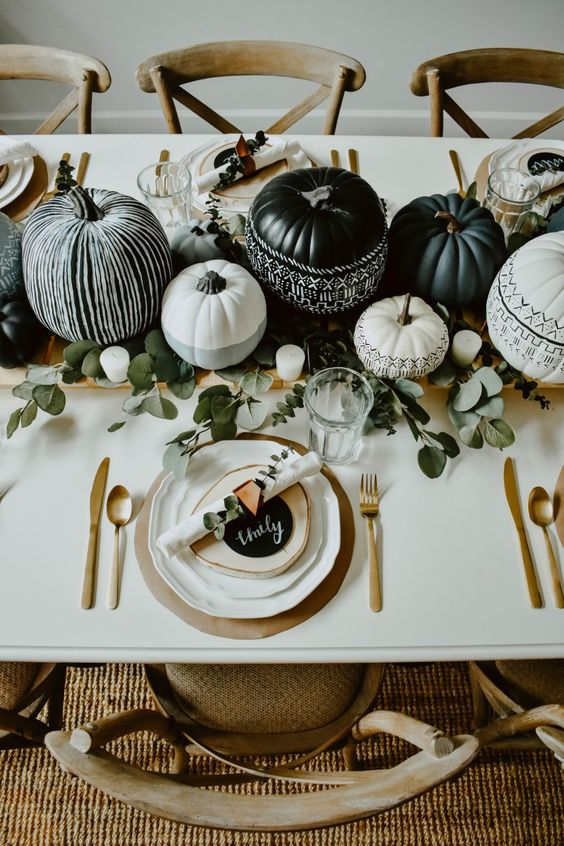 a stylish modern Halloween tablescape with grey, black and white pumpkins, eucalyptus, gold cutlery and chargers