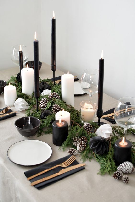 a stylish modern black and white tablescape, with black and white candles, snowy pinecones, metallic cutlery, dark bowls and white plates
