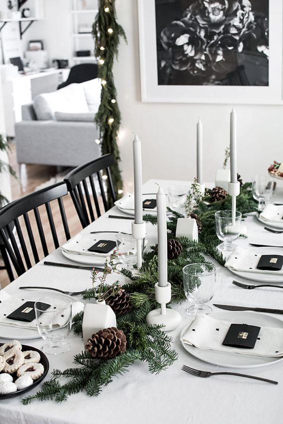 a stylish monochromatic winter table with an evergreen and pinecone runner, grey candles, white house vases, polka dot napkins