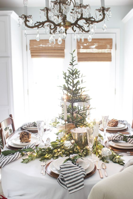 a stylish winter table with a Christmas tree, an evergreen and light runner and striped napkins