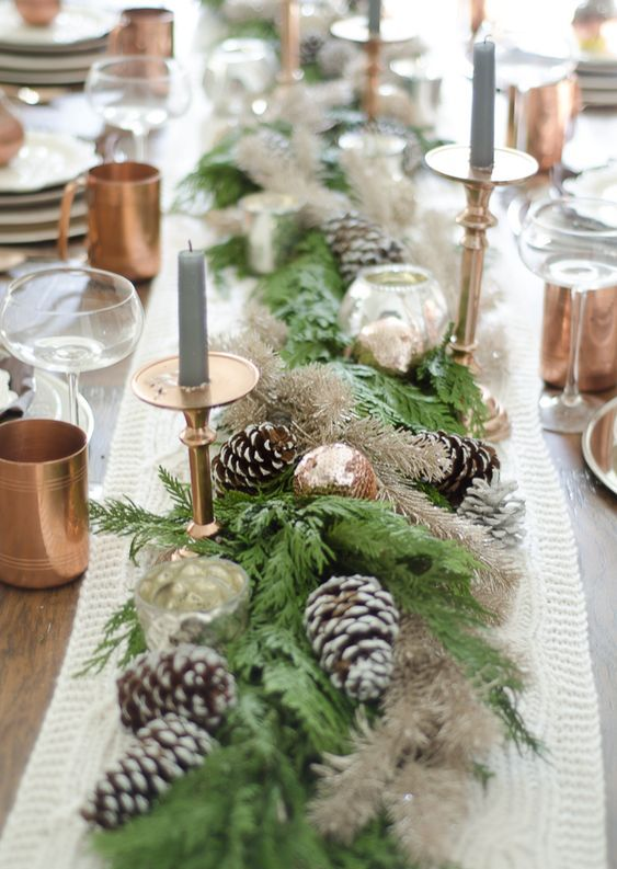 a stylish winter table with a knit runner, evergreen and snowy pinecone runner, grey candles, copper mugs and ornaments