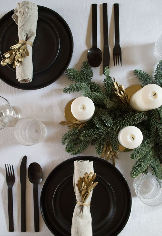 a stylish winter tablescape with evergreens, pillar candles, black plates and chargers and cutlery plus gold branches