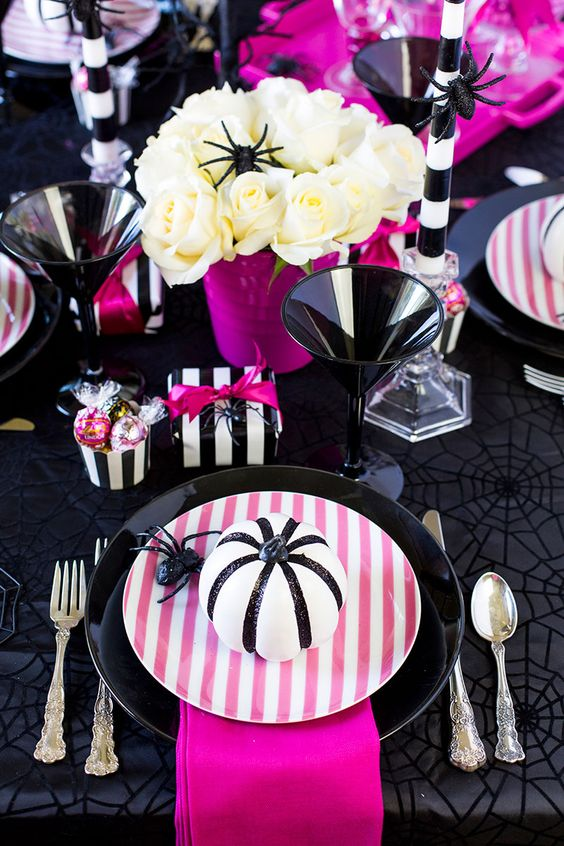 a super bright modern Halloween tablescape in black, white and hot pink, white roses, pink plates, napkins and other detailing