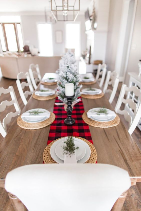 a very simple and cozy winter table with a plaid runner, woven palcemats, evergreens and a snowy Christmas tree