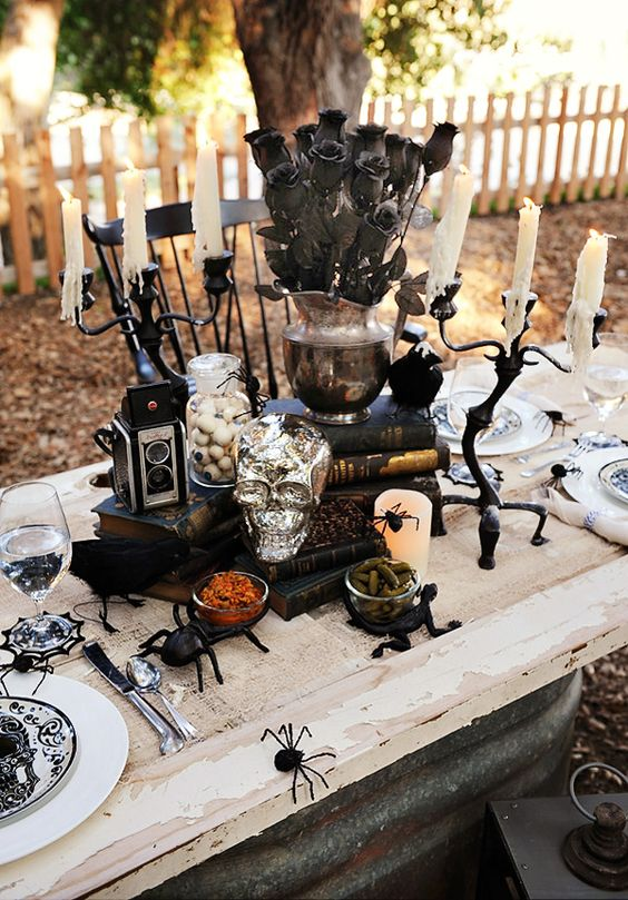 a vintage Halloween table setting with spiders, a silver skull, black blooms, vintage cameras and printed plates