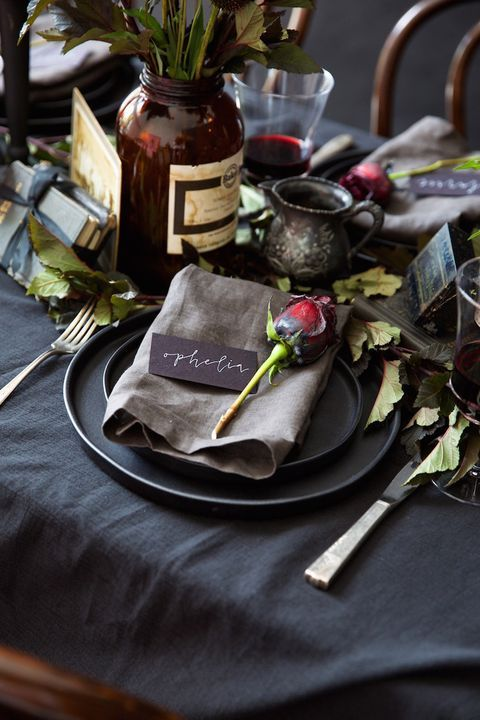 a vintage Halloween tablescape with black linens and plates, leaves and red roses, vases and candles