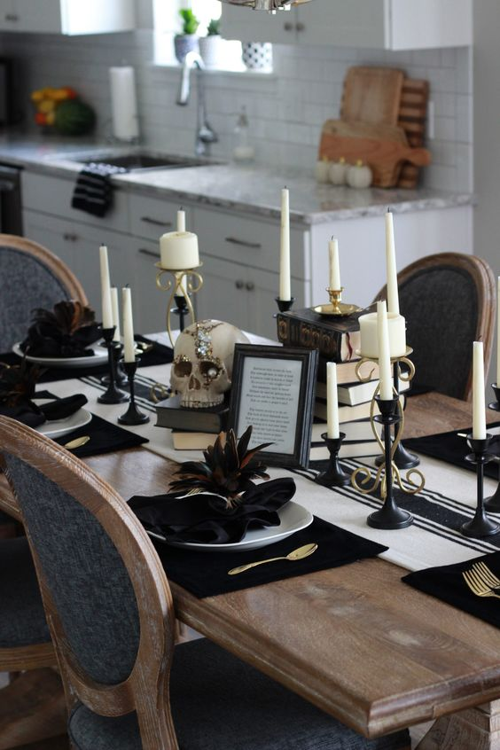 a vintage glam Halloween tablescape with a striped runner, stacks of books, candles in black candleholders, white porcelain and dark feathers