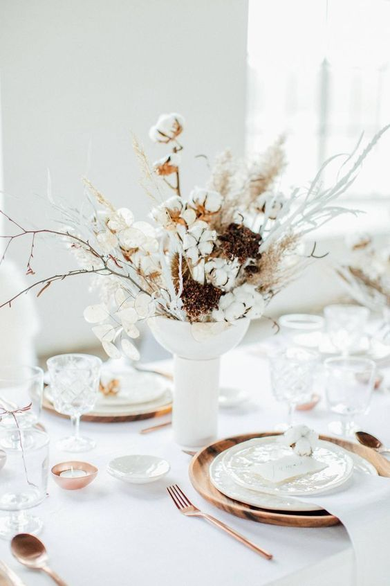 a warming up winter table with a dried herbs and cotton centerpiece, wood chargers, copper candleholders and cutlery